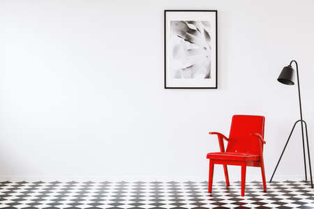 Red armchair next to black lamp on checkerboard floor in empty interior with poster and copy space. Place for your table