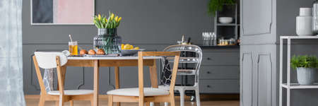 Plastic chair at a wooden table with yellow flowers in modern dining room interior with grey cabinet Stock Photo