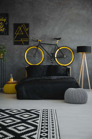 Bike above black bed in modern grey bedroom interior with patterned carpet, pouf and lamp. Real photo Stock Photo