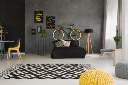 Bicycle above black bed in dark open space interior with pouf and yellow chair at desk. Real photo