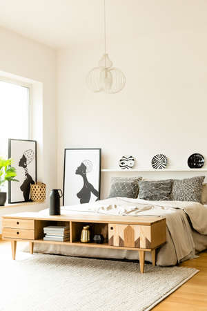Patterned plates above bed in boho bedroom interior with posters and wooden rustic cupboard