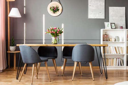Wooden dining table, grey chairs, bookshelf and pink tulips in dining room interior