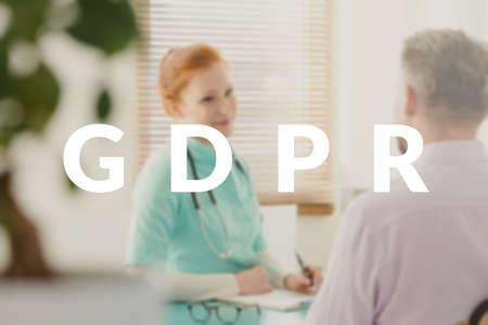 Young, female doctor explaining new GDPR related policy to her patient. White text on a blurred photo Stock Photo