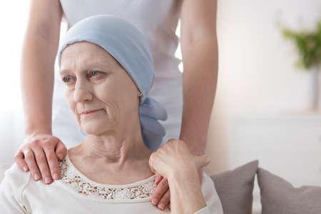Weinende ältere Frau mit Krebs und ein Freiwilliger, der sich um sie kümmert