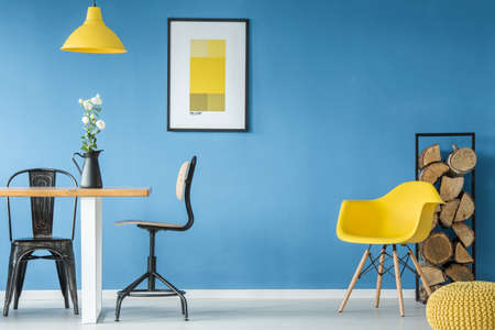 Blue wall with a yellow poster in dining room interior with table, chairs and firewood log rack
