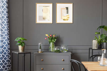 Flowers on grey cabinet under posters in minimal loft interior with plants. Real photo Reklamní fotografie - 102916581