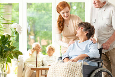 Caregiver and senior man supporting disabled elderly woman in the nursing house