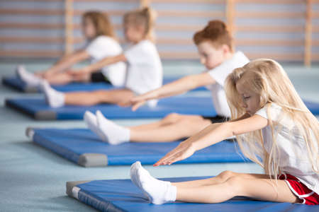 Blonde girl stretching on a blue mat during physical education classes Stock Photo