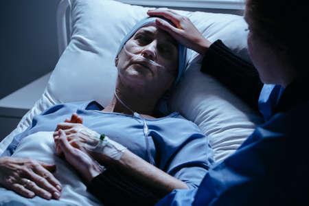 Cuidador apoyando a una mujer enferma con cáncer que muere en el hospital