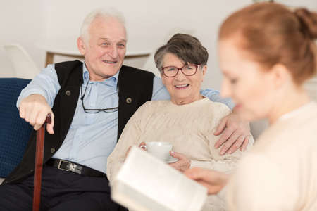 Professional caregiver assisting senior couple in daily activities at home