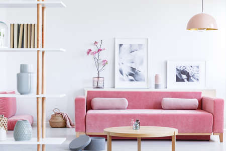 Posters and flowers above pink sofa in pastel living room interior with wooden table. Real photo