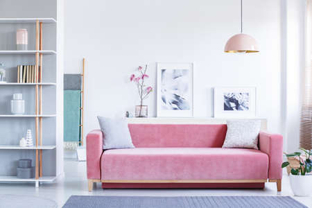 Lamp above pink settee with pillows in pastel living room interior with flowers and posters. Real photo