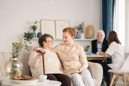 Professional caregivers assisting seniors during daily activities in an old age home Stock Photo