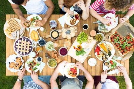 Top view of friends sitting at the table and eating Italian food Stock Photo