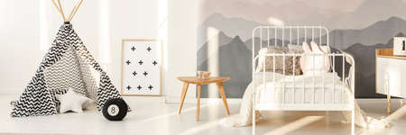 Patterned tent near white metal bed in kids bedroom interior with mountain wallpaper