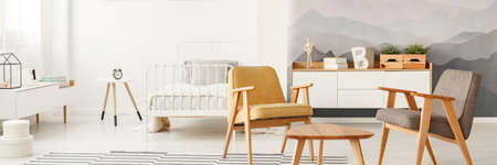Grey and yellow wooden armchairs in bright open space interior with metal bed near clock on a table