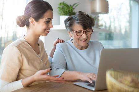 Happy assistant teaching an elderly woman searching the Internet on a laptop