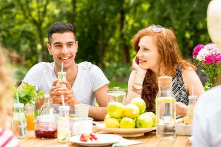 Beautiful girl looking at her boyfriend while having lunch with friends in the garden Stock Photo