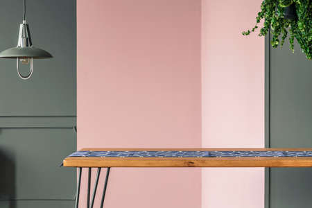 A wooden table standing in a dining room interior with grey and pink wall under a hanging lamp and a plant
