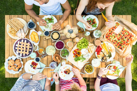 High view of a table with Italian food, eaten by young group of friends outdoors Stock Photo