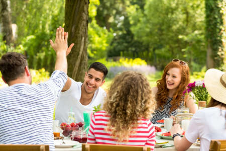 Man giving a high five to a friends and girls laughing during lunch in the garden