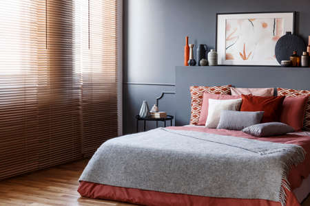 Window blinds in a bedroom interior with a king size bed, cushions, painting and vases