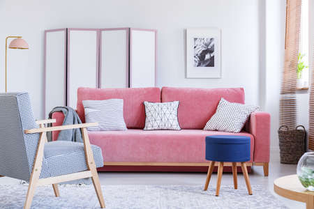 Blue stool next to pink couch in bright living room interior with armchair and poster. Real photo