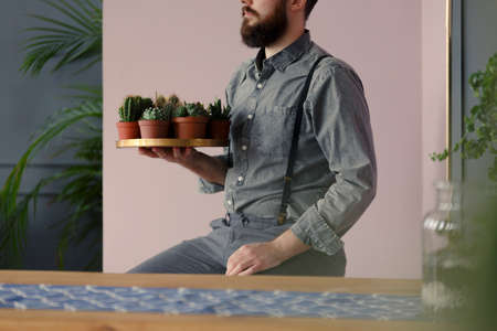Close-up of hipster with beard holding a gold plate with succulents and cacti at home