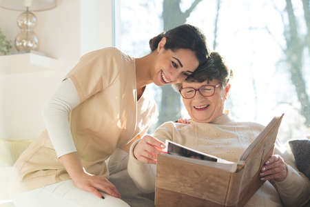 Smiling senior woman watching photo album with happy caregiver Stock Photo