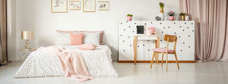 Bedside table with glass lamp standing next to king-size bed with dotted sheets, pink pillows and blanket standing in white bedroom interior with posters, fresh plants and dressing table with telephone Stock Photo