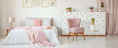 Dotted bedding on double bed placed in white room interior with green plants, fresh tulips, simple posters and pastel pink armchair