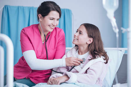 Smiling nurse with stethoscope examining happy girl in the hospital