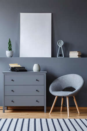 Grey armchair next to cabinet in apartment interior with mockup of empty poster. Real photo Stock Photo