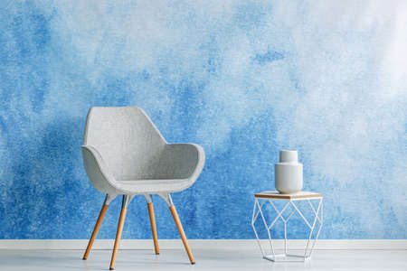 Copy space room interior with simple gray armchair and openwork side table with a dish on top against blue and white color ombre wall. Real photo. Stock Photo