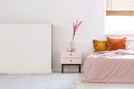 Real photo of a pink, feminine bedroom interior with orange cushions on bed and flowers on a nightstand next to an empty wall Stock Photo