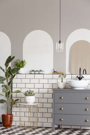 Real photo of a cupboard with a washbasin standing next to plants in a bathroom interior with white tiles on a wall and patterned floor