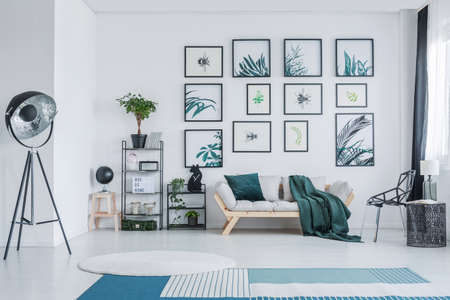 Big studio lamp standing in white living room interior with wooden sofa with green pillow and blanket, gallery with simple posters, black racks with plants and two carpets on the floor Stock Photo