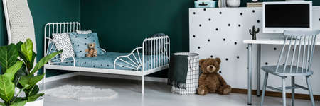Green kids bedroom interior with metal bed, computer on desk and teddy bear sitting next to patterned basket Stock Photo