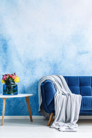 Comfortable dark blue settee with gray blanket and small side table with fresh flowers in a vase against blue and white ombre wall in a living room interior. Copy space background. Real photo.