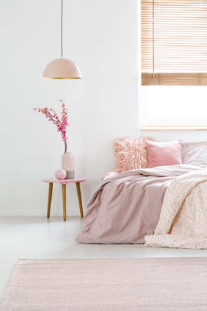 Real Photo Of Flowers On A Bedside Table Peach Lamp And Pink Bed In Simple