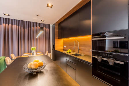 Black kitchen with light in modern dark interior with drapes and flowers on a dining table Imagens