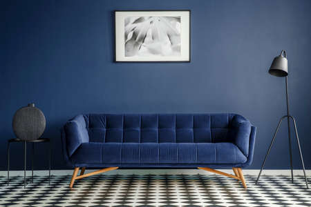 Navy blue room interior with comfortable plush couch in the middle, black lamp and side table with decoration standing on chessboard floor. Framed image on the wall. Real photo Standard-Bild - 103023854
