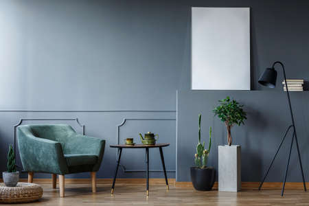 Black table between green armchair and plants in grey interior with mockup of empty poster. Real photo Stock fotó