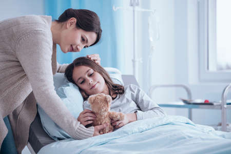 Caring mother giving a plush toy to sick daughter lying in a hospital bed