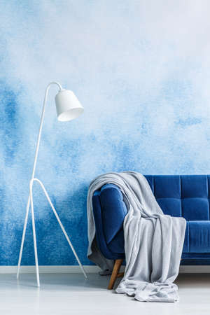 Navy blue couch with gray blanket and white standing lamp against blue and white ombre wall in a living room interior. Real photo. Stock Photo