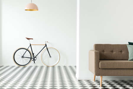 Bike against an empty wall, cropped sofa and checkered floor in an anteroom interior Stock Photo