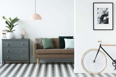 Chest of drawers next to a sofa with pillows and patterned floor in living room interior with a bike and painting at the front Standard-Bild - 103036479