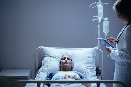 Doctor with tablet next to bed with dying elderly woman with cancer in the clinic Stock Photo