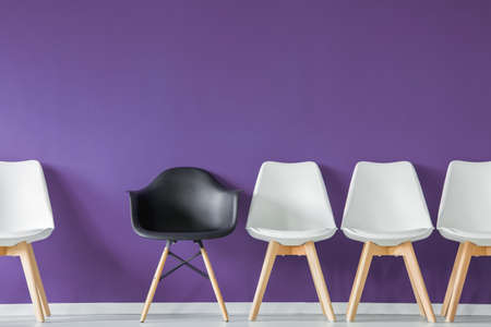 One black chair in a row with white chairs isolated on an ultra violet background in a lobby interior