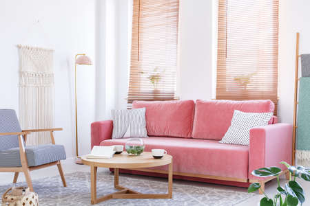 Patterned armchair next to pink sofa in bright flat interior with wooden table and blinds. Real photo
